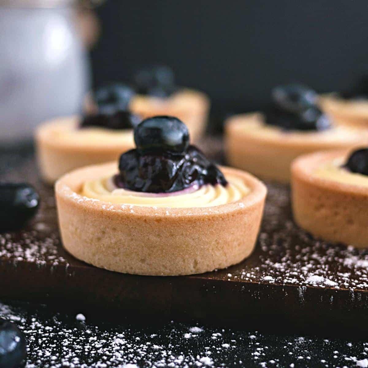 A few mini tarts o a wooden board.