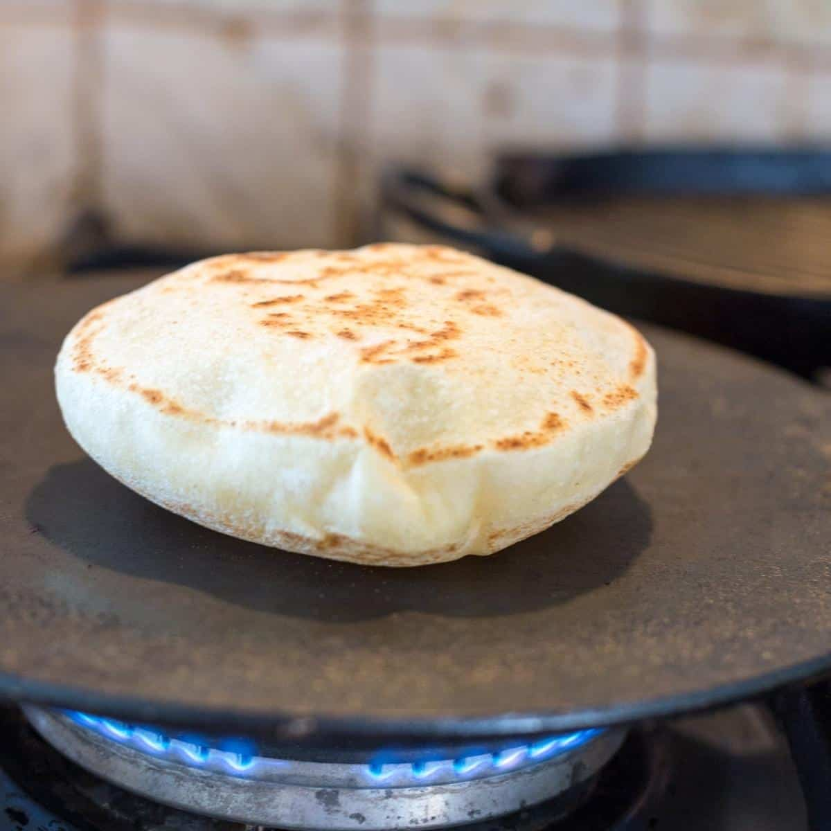 A pita cooking on the skillet.
