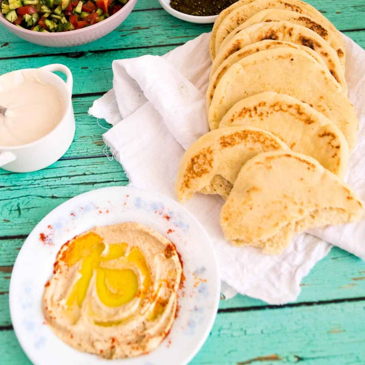Hummus and pita bread on a table.