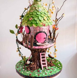 An enchanted forest tree house cake would make lovely celebration such as birthday or bat mitzvah cake for a young girl. This gravity-defying cake built on a tree trunk and surrounded by flowers, butterflies, and twigs has a little sing, pink ladder, and blossoms for that enchanted forest look. Here are a few details on how I made this cake.