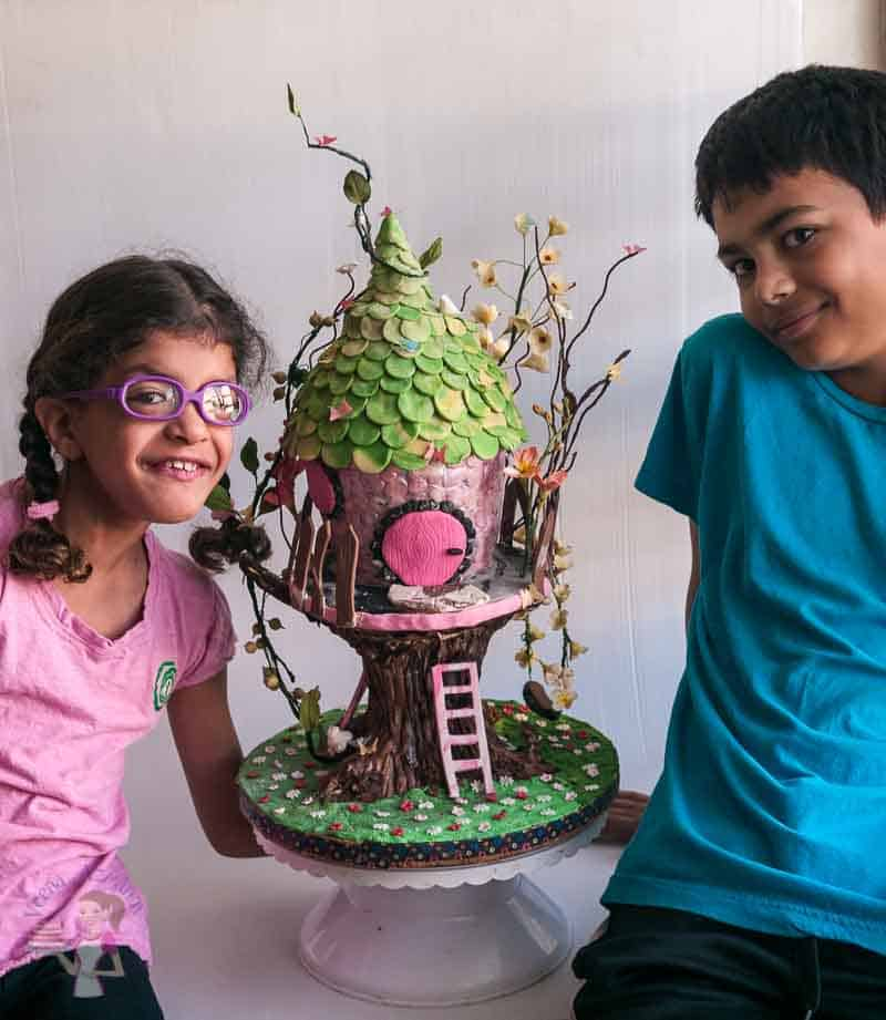 A cute little girl and a handsome boy sitting next to a tree house cake.