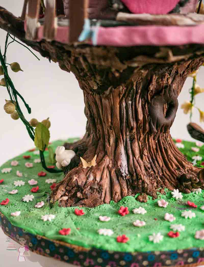 A close up of the trunk of a tree house cake.