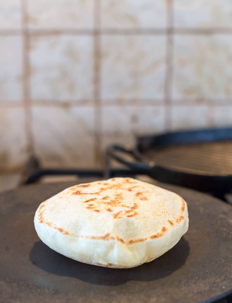 A close up shot of the puffed up pita bread on the hot skillet - a simple easy and effortless recipe to make perfect homemade pita bread