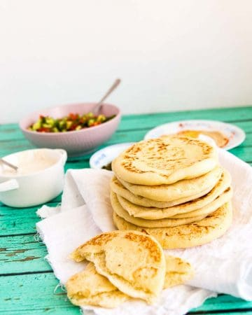 A stack of pita bread on a table.