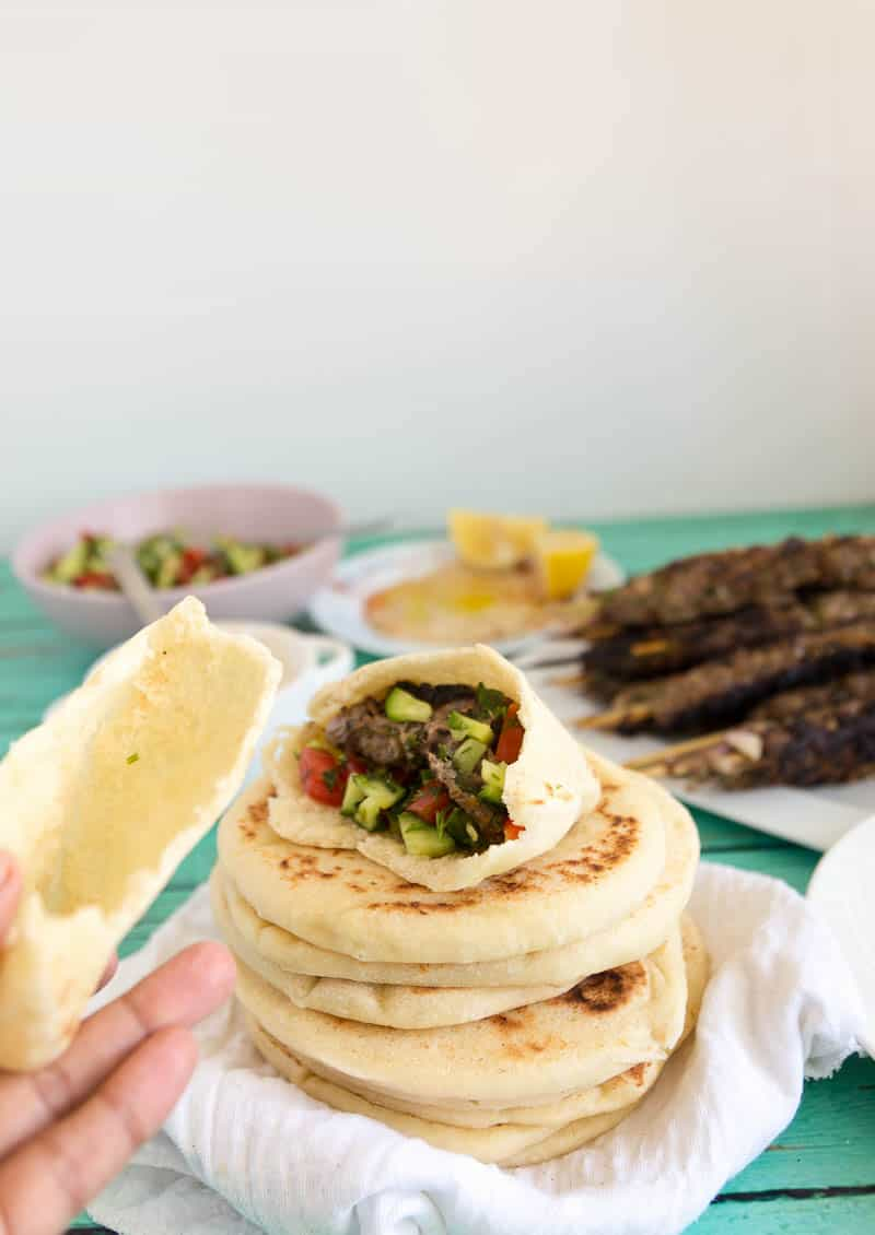 A pile of homemade easy pita bread with a stuffed pita pocket stuffed with beef kebabs and salad.