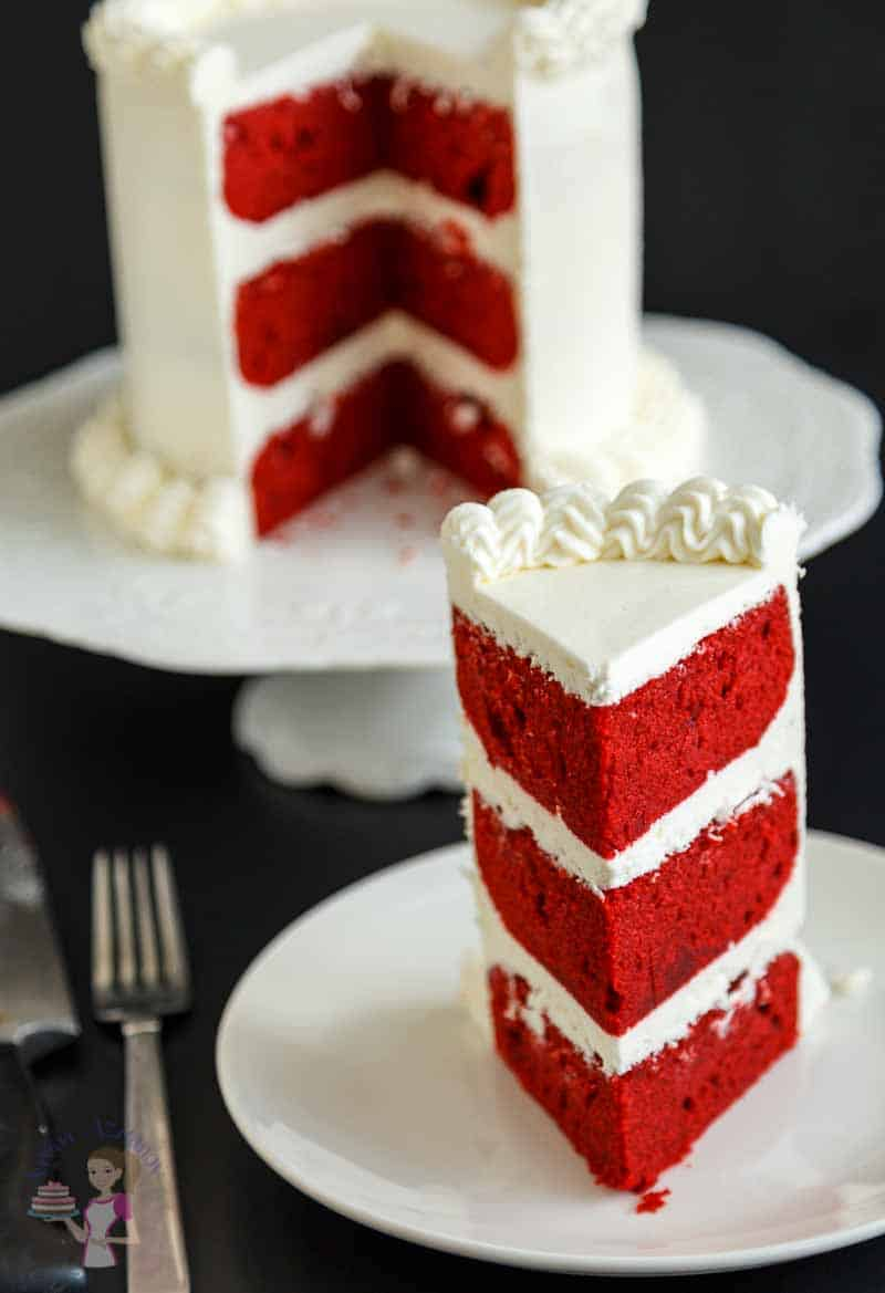 A top view of this classic red velvet cake with cream cheese frosting showing a cut slice of the perfect cake.