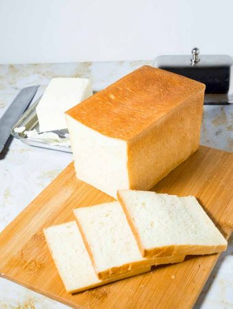 A Pinterest Optimized image for Pullman Sandwich Bread a famous French Pain De Mie bread featuring a loaf of bread cut into slices