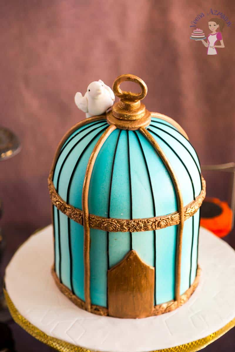 A top view of this vintage birdcage cake tutorial made in turquoise and metallic gold with a gum paste bird