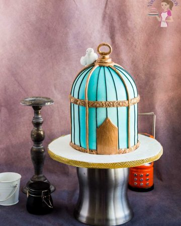 A vintage birdcage cake on a cake stand.