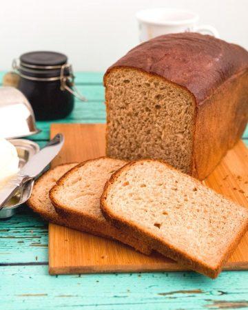 A sliced sandwich bread on a wooden cutting board.
