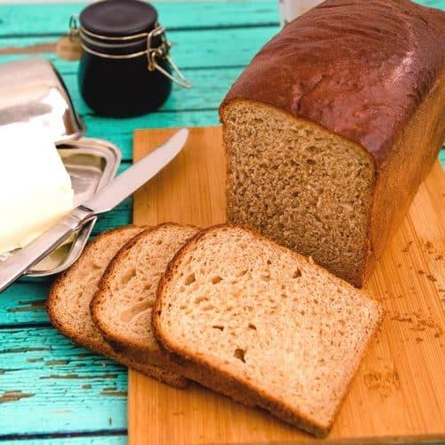 A sliced sandwich bread on a wooden board.