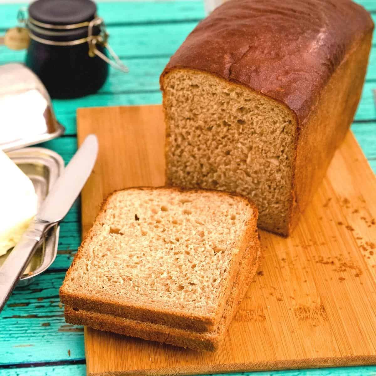 Sliced whole wheat sandwich loaf bread on a wooden board.