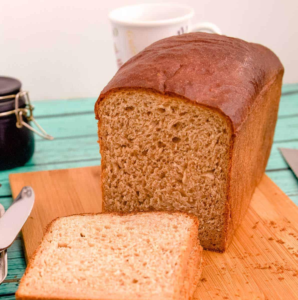 A loaf of sandwich bread on a wooden board.