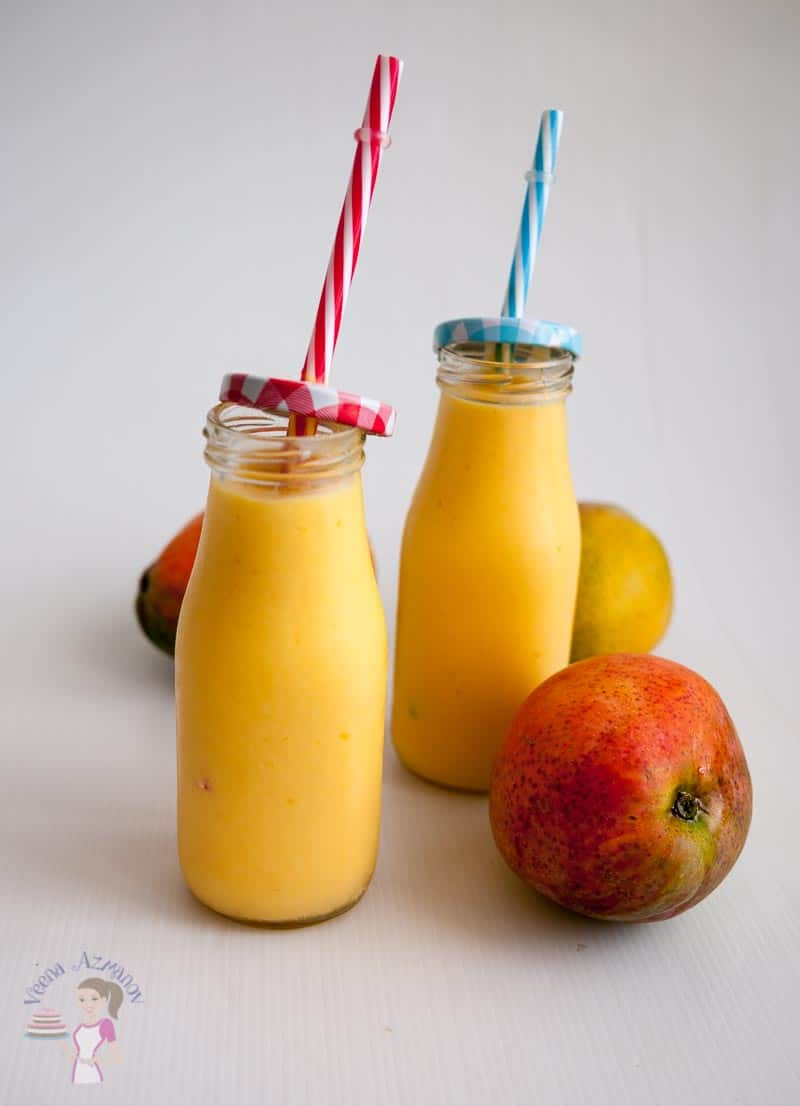 A Pinterest Optimized Image for Coconut Mango Lassi featuring two full milk bottle shaped glasses with a lid and straws
