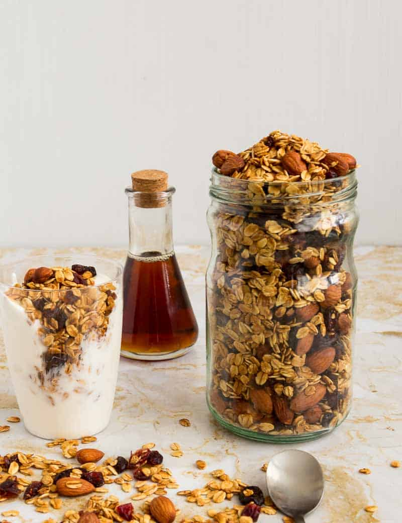 A jar full with granola next to a glass of yogurt with granola on top.