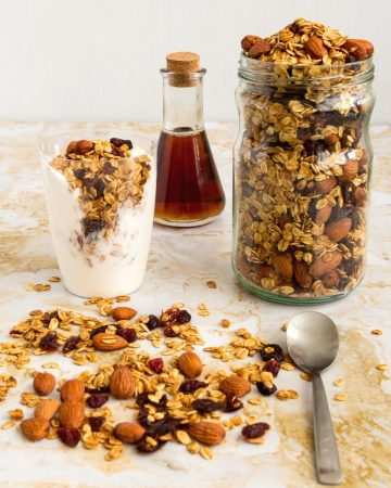 A jar filled with granola next to a glass of yogurt with granola on top.