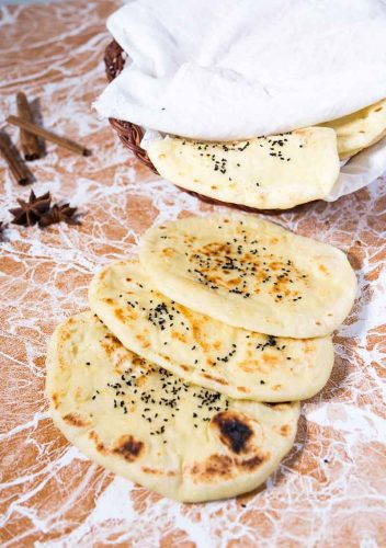 A garlic butter naan is a variation on the classic Indian naan recipe that is often accompanied with an Indian meal. This simple, easy and effortless recipe makes a deliciously soft and chewy garlic butter naan that just melts in the mouth.