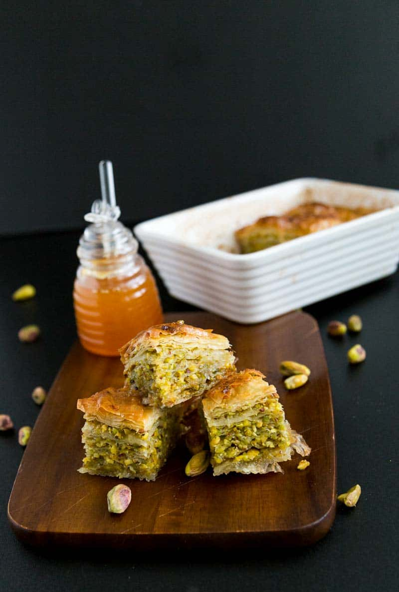 A shot of the baklava pan in the back with three squares on a wooden board showing the gorgeous green pistachio filling for our honey pistachio baklava.