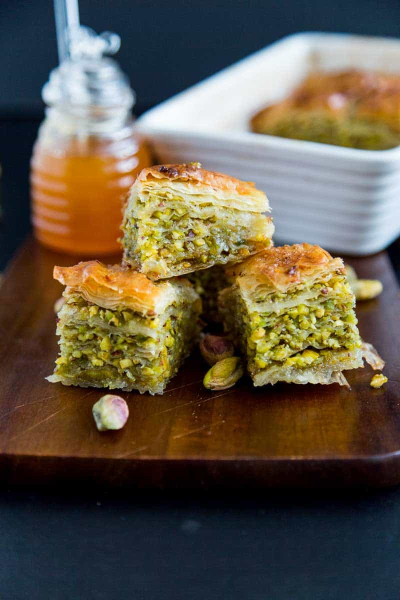 Three squares of honey pistachio baklava that just melts in the mouth. Close up of the layers showing the layers in between