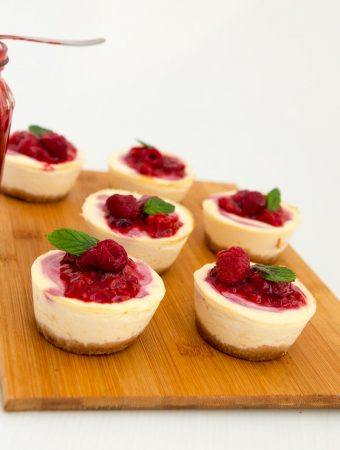 A Pinterest Optimized Image for mini raspberry cheesecakes, a custard based cheese dessert featuring six mini raspberry flavored cheesecakes with a bottle of raspberry filling