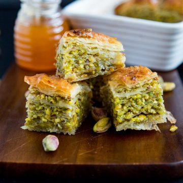 3 squares of baklava on a wooden tray.