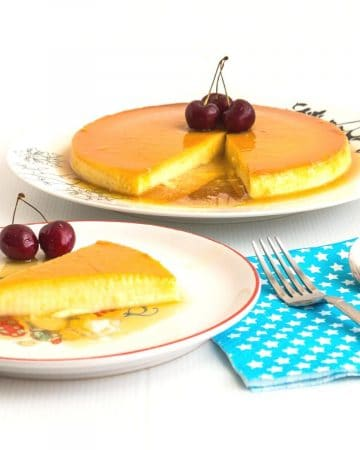 A slice of apricot flan on a plate, with the remaining flan on a serving plate.
