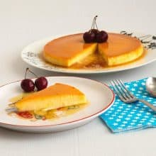 A slice of apricot flan on a plate with cherries.
