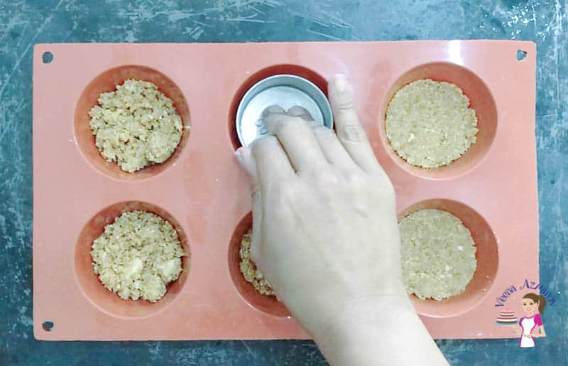 Press the cookie crumbs in the prepared muffin pan for cheesecake batter