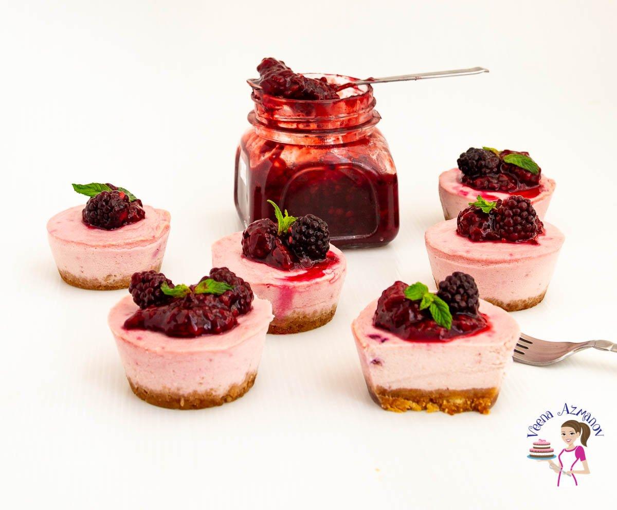 Mini blackberry cheesecakes on a table.