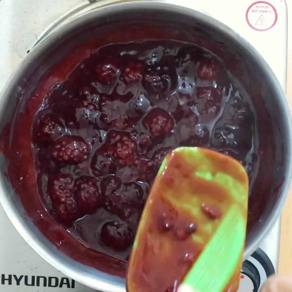 Saucepan and spatula making fruit filling.