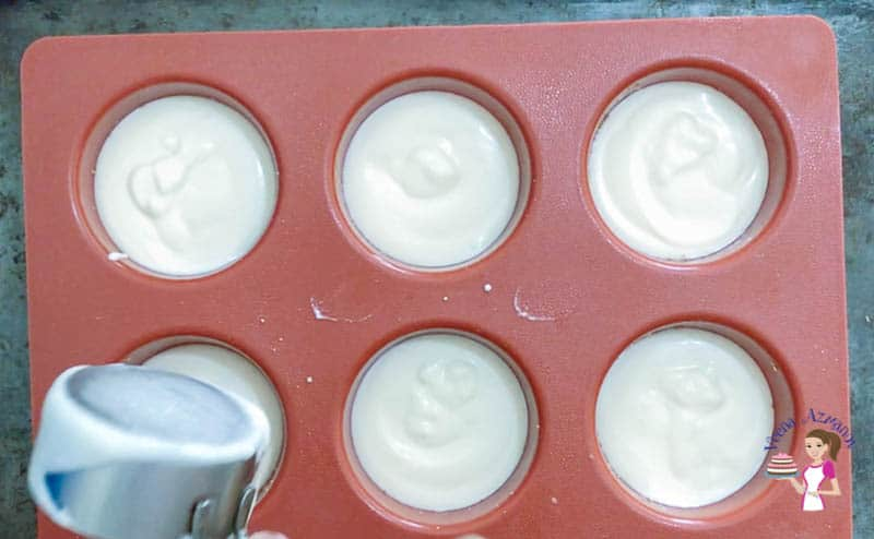 Filling the pan with the cheesecake batter for the mini cheesecakes