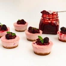 Mini cheesecakes with a mason jar of blackberry filling.