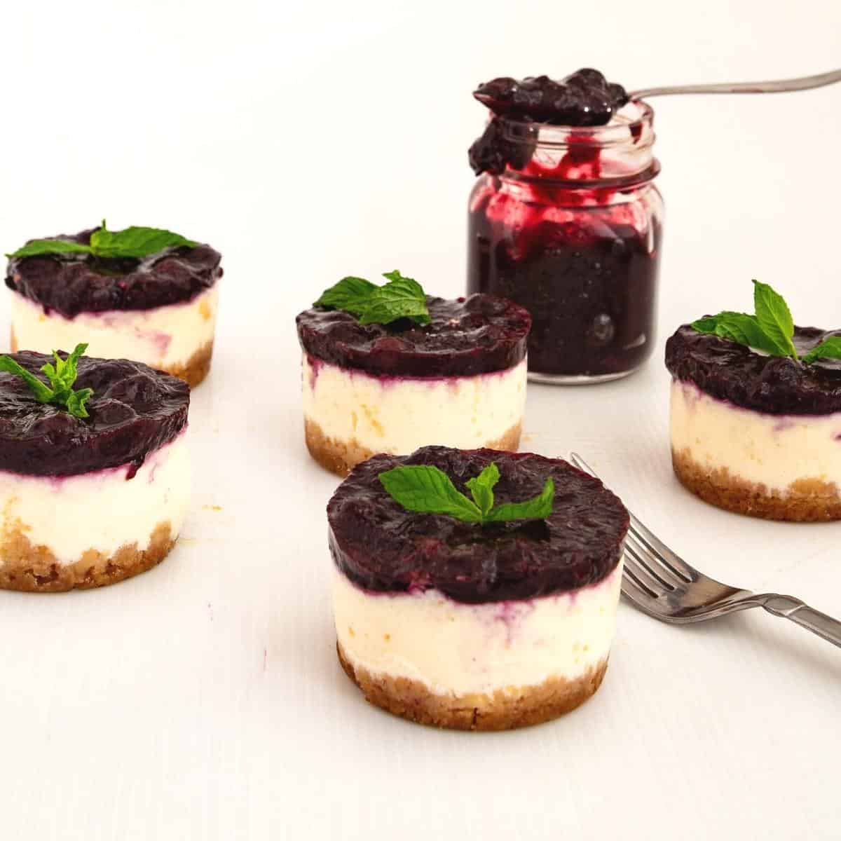 Mini cheesecakes topped with blueberry filling on the table.
