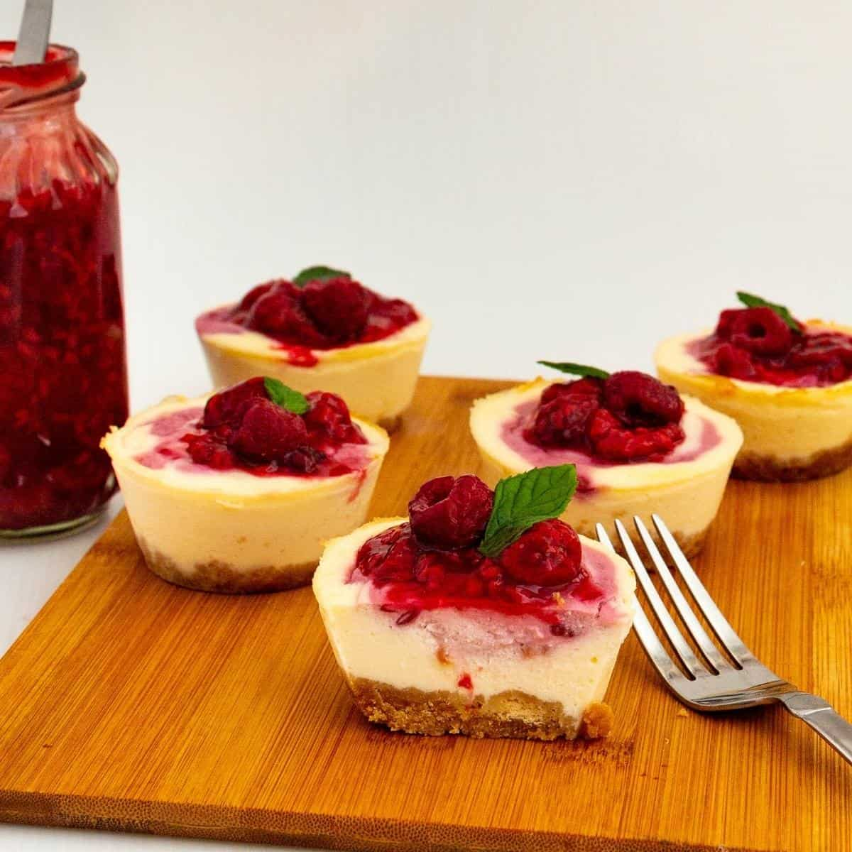 Sliced mini cheesecakes topped with raspberries.