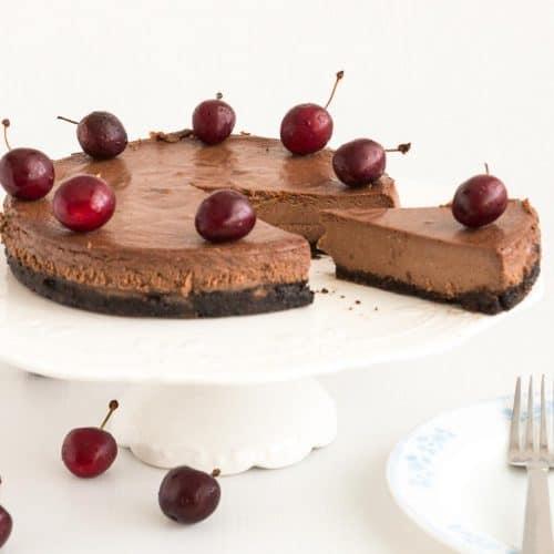 Sliced chocolate cherry cheesecake on a cake stand.