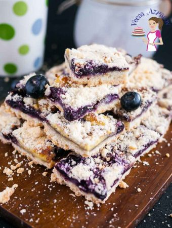 A stack of blueberry cake squares on a wooden board.