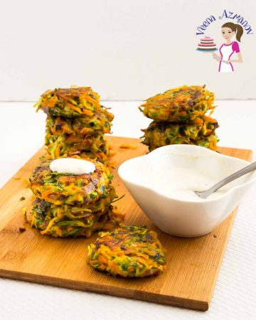 Stacks of carrot zucchini patties on a wooden board.