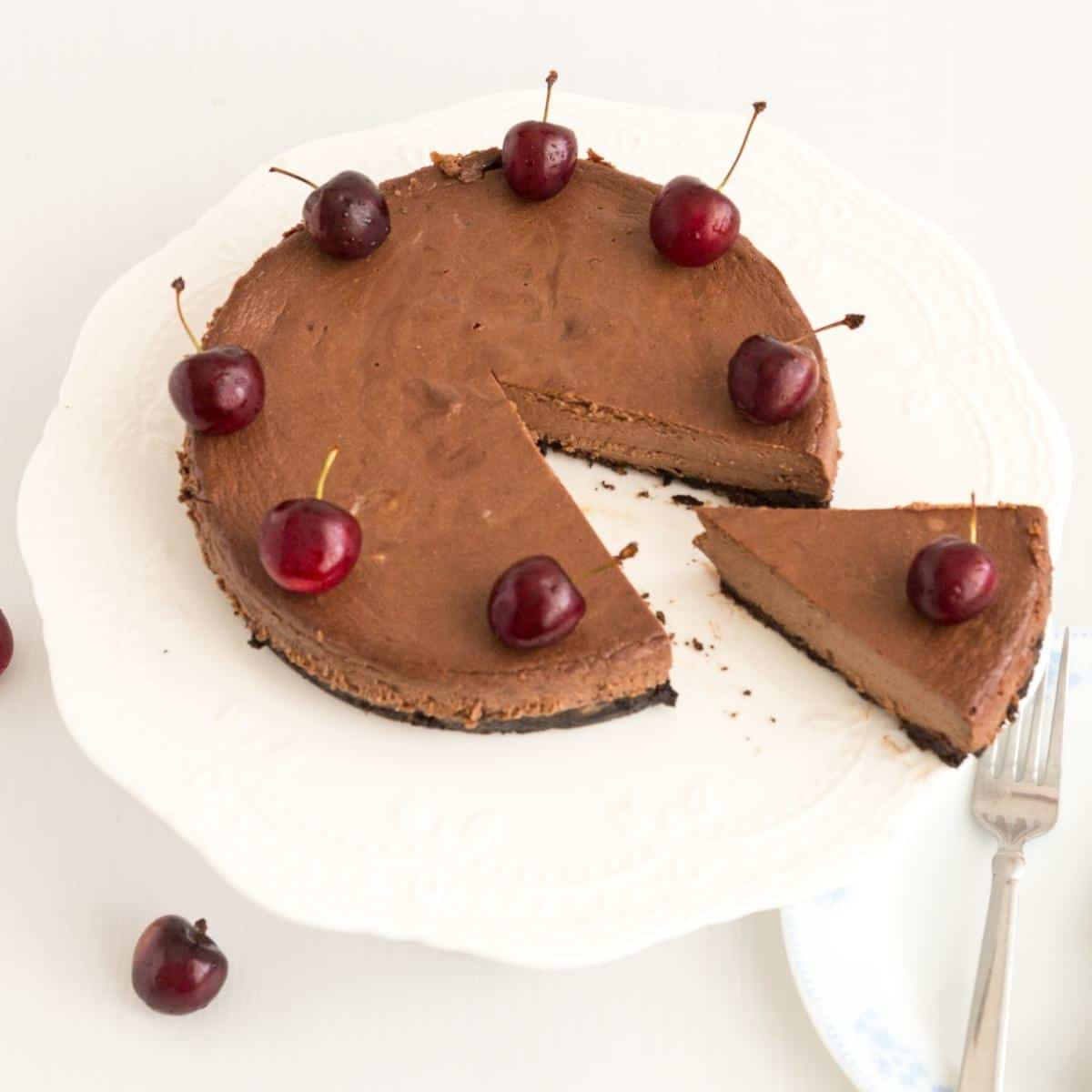 Sliced chocolate cheesecake with cherries on a cake stand.