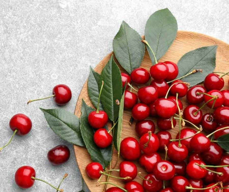 A pile of cherries on wooden board.