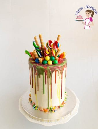 An image optimized for social sharing for this loaded lollipop rainbow drip cake with a rainbow cake recipe on the inside and perfect chocolate drip cake on the out.