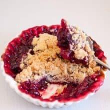 A ramekin and spoon with raspberry fruit crumble.
