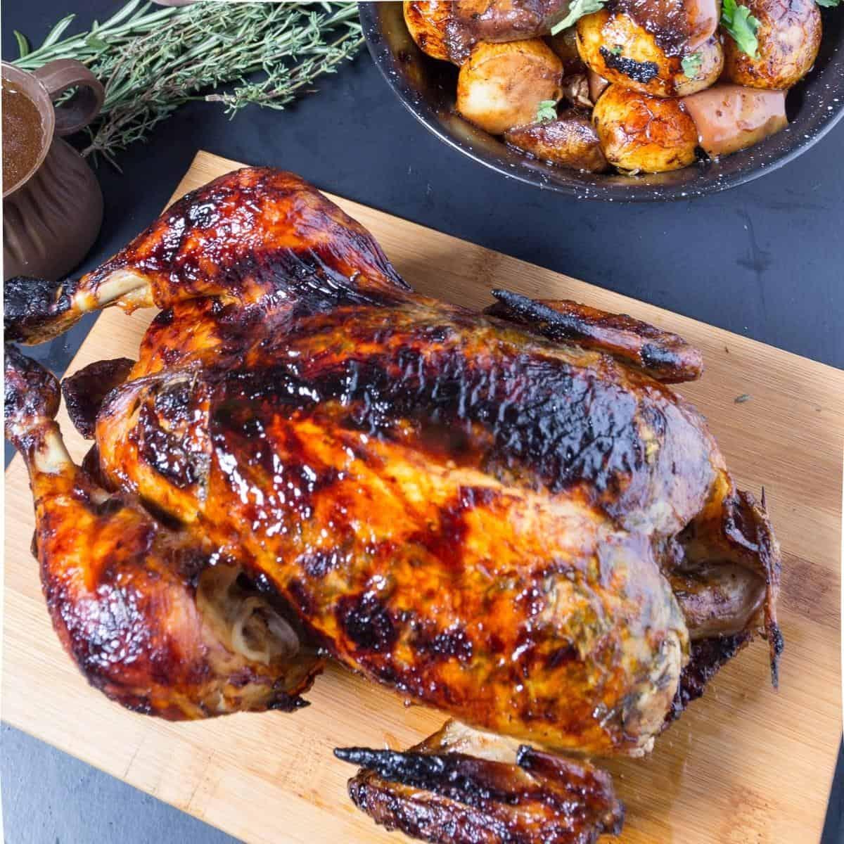 A roast chicken on a wooden board