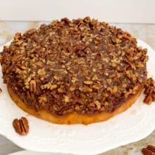 An inverted pecan pie cake on a cake stand.