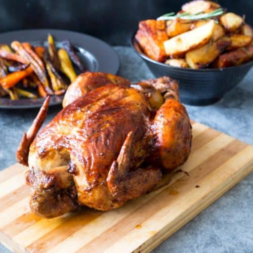 A wooden board with roasted chicken