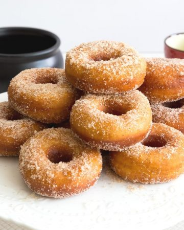 A stack of sugar donuts on a cake stand.