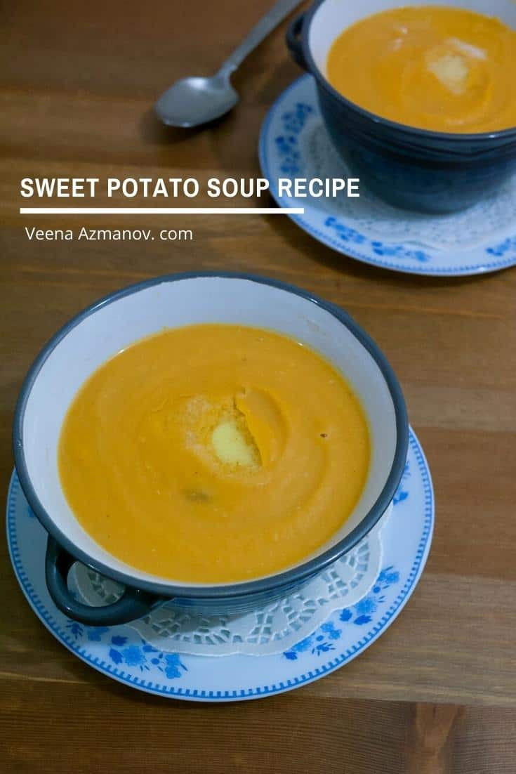 A cup of sweet potato soup on a table.