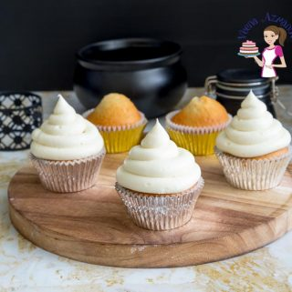 Cupcakes with buttercream frosting on a round board.