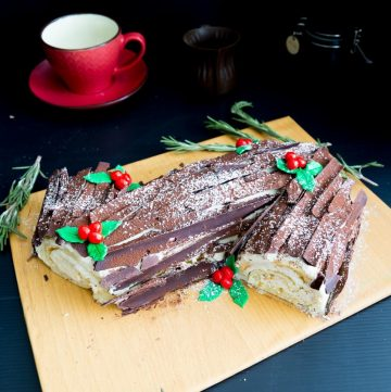 A Swiss cake with chocolate bark on a cake board