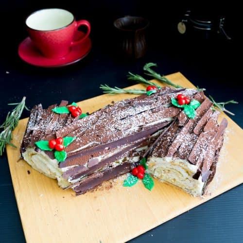 A Swiss cake with chocolate bark on a cake board