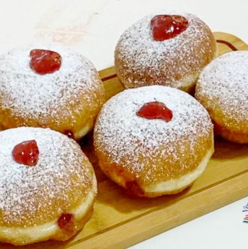 Doughnuts filled with jam on a wooden board